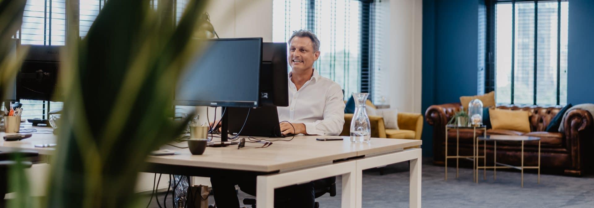 Wouk witte eigenaar Freelancefactoring achter zijn bureau